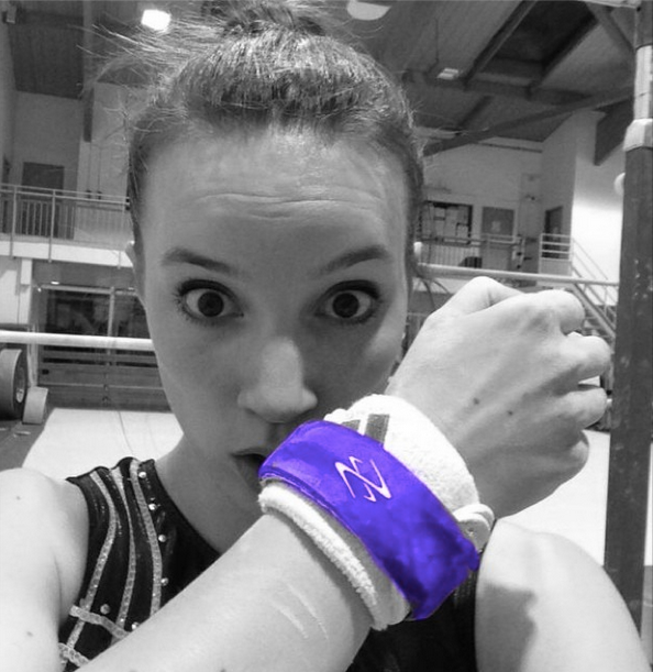 gymnast wearing bands on her grips in purple