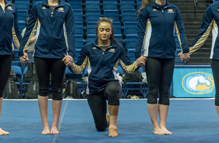 gymnast kneels in protest of police brutality while competing for UC Davis gymnastics team